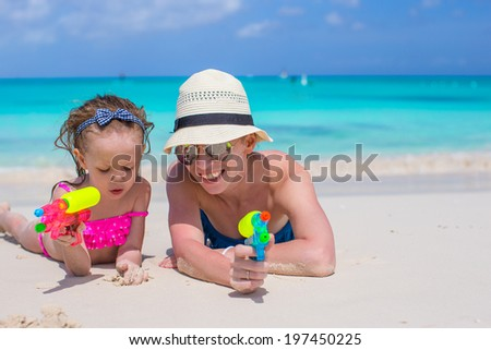 Happy mother and little girl at tropical beach having fun - stock photo