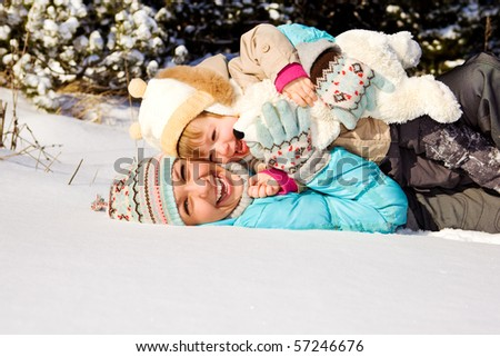 Happy mother and little girl lying in snow - stock photo