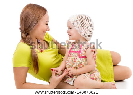 happy mother and little girl lying on white floor and smiling