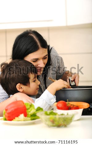 Happy mother and little son in the kitchen, happy time and togetherness - stock photo