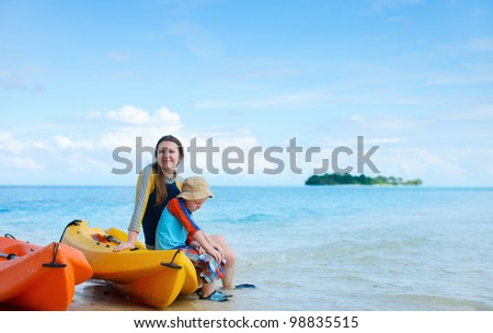 Happy mother and son after kayaking relaxing at beach - stock photo