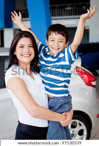 Happy mother and son buying a car - stock photo
