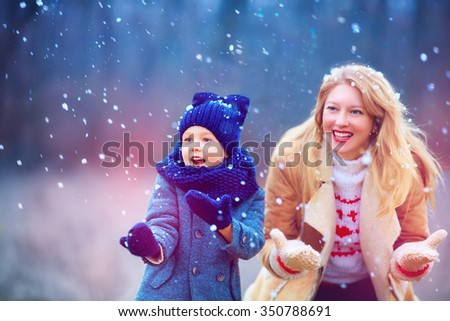 happy mother and son having fun under winter snow - stock photo