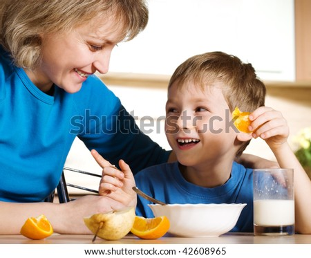 Happy mother and son in kitchen - stock photo
