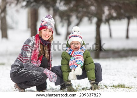 Happy mother and son in winter park having fun. focus on mother - stock photo