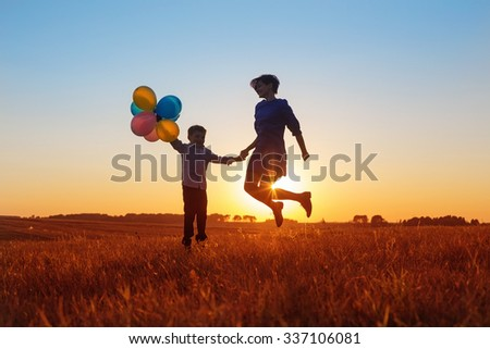 happy mother and son jumping with balloons outdoor - stock photo