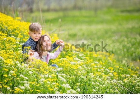 Happy mother and son laughing together outdoors. soft daylight - stock photo
