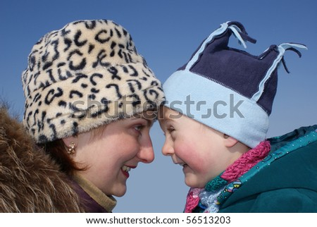 Happy mother and son look at each other - stock photo