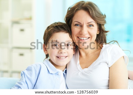 Happy mother and son looking at camera - stock photo