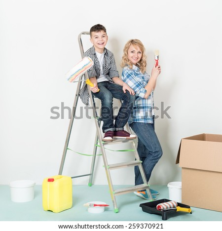 Happy mother and son makes repairs at home. - stock photo