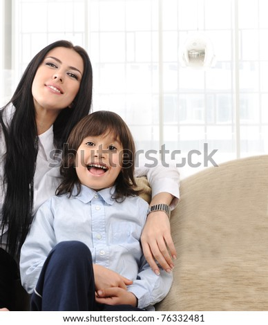 Happy mother and son on sofa sitting together - stock photo