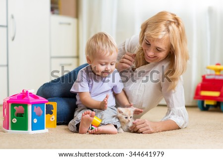 Happy  mother and son play together with kitten at home - stock photo