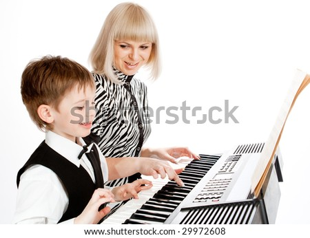 Happy mother and son playing electric piano - stock photo