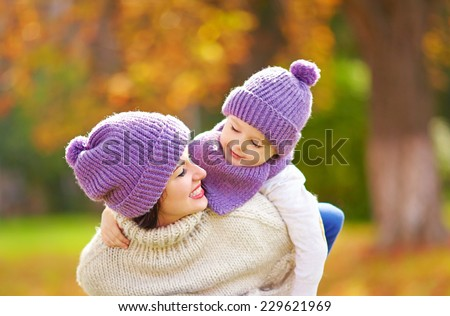 happy mother and son playing in autumn park - stock photo