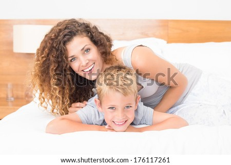 Happy mother and son posing on bed looking at camera at home in bedroom - stock photo