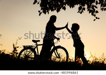 happy mother and son riding bike at sunset