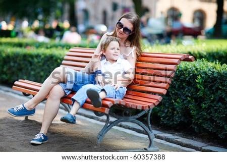 Happy mother and son sitting on bench in city park on summer day