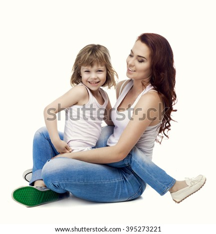 happy mother and son sitting on the floor, isolated against white studio background - stock photo