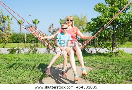 Happy mother and son sitting on the hammock - stock photo