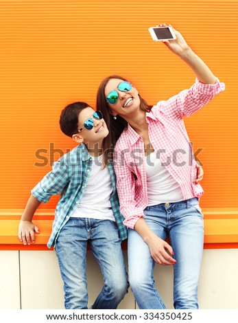 Happy mother and son teenager taking picture self portrait on smartphone in city, over colorful background, wearing a checkered shirt and sunglasses  - stock photo