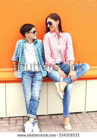 Happy mother and son teenager wearing a checkered shirt and sunglasses having fun in city - stock photo