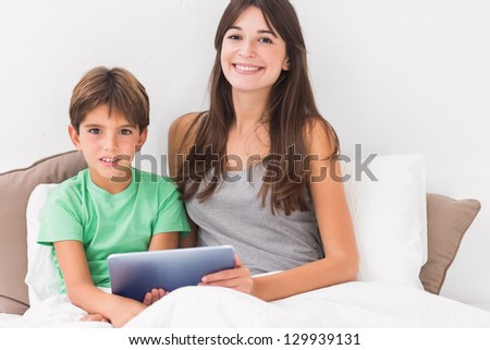 Happy mother and son using digital tablet in bed