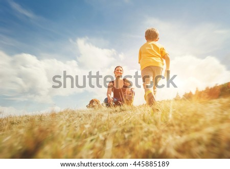 Happy mother and son walk on the golden field with dog - stock photo