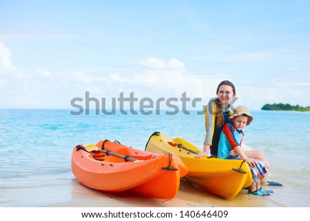 Happy mother and son with kayaks at tropical beach - stock photo