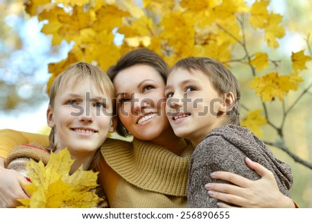 Happy Mother and sons in the autumn park
