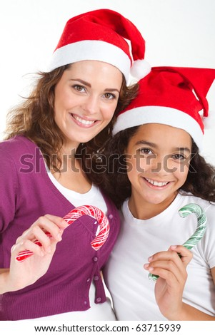 happy mother and teen daughter holding christmas candy cane - stock photo