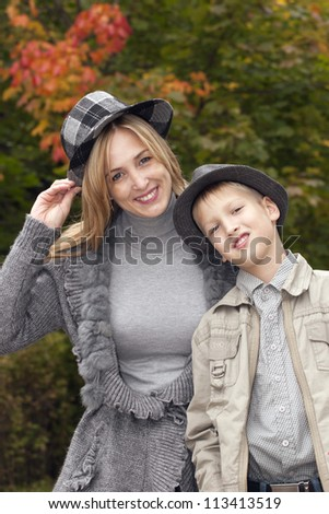 Happy mother and the son in hats in park - stock photo
