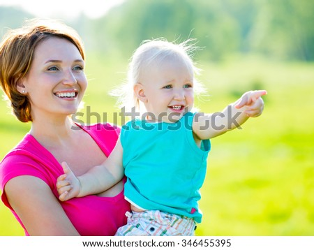 Happy mother and toddler son at field -  outdoor portrait - stock photo
