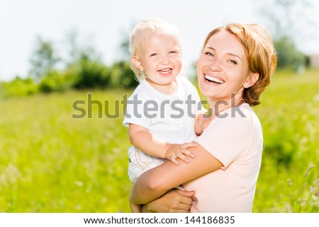 Happy mother and toddler son in the spring meadow outdoor portrait - stock photo