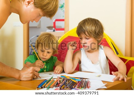 Happy mother and two children sketching on paper in home interior