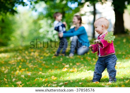 Happy mother and two kids spending time outdoors at sunny autumn day - stock photo