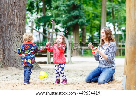 Happy mother and two little children playing together on playground in summer. Funny toddler boy and girl, siblings having fun together - stock photo