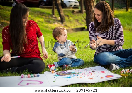 Happy Mother aunt sister and son child painting in the park. - stock photo