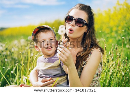 Happy mother blowing a dandelion - stock photo