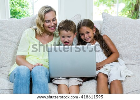 Happy mother by son and daughter using laptop on sofa at home - stock photo