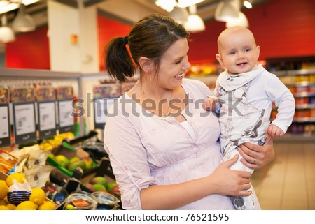 Happy mother carrying child in supermarket - stock photo
