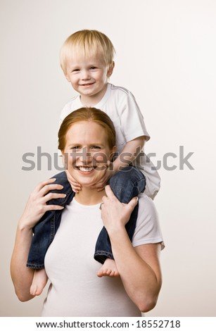 Happy mother carrying son on her shoulders playfully