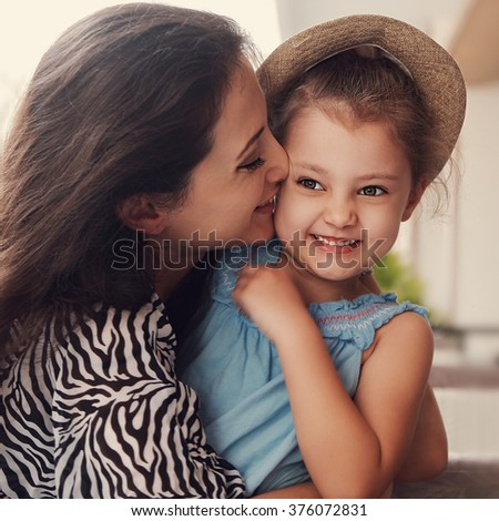Happy mother cuddling and kissing her cute kid girl in hat. Toned closeup portrait of happiness and love - stock photo