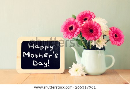 happy mother day written on chalkboard next to flowerpot with fresh flowers ,  - stock photo