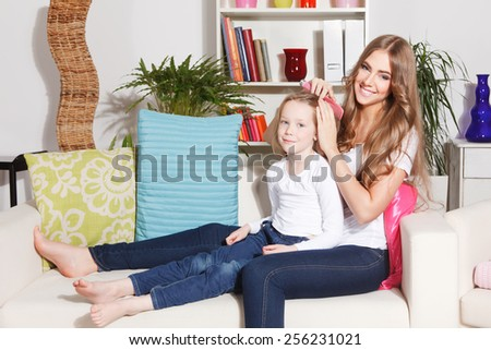 Happy mother doing daughter's hairdo - stock photo