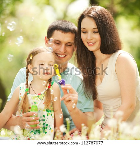 Happy mother, father and daughter blowing bubbles in the park