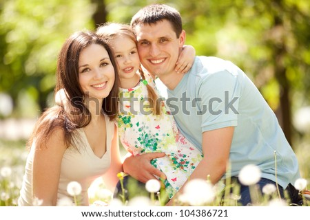 Happy mother, father and daughter in the park - stock photo