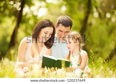 Happy mother, father and daughter read a book in the park - stock photo