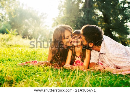 Happy mother, father and  kissing their daughter in the park - stock photo