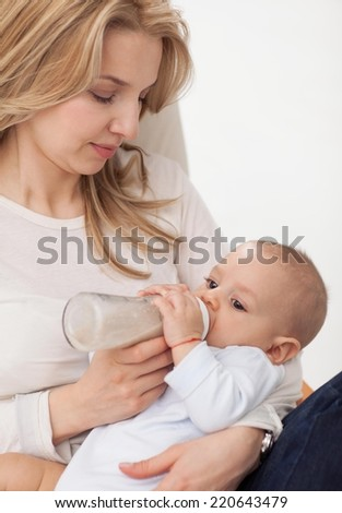Happy mother feeding her 6 months old son.