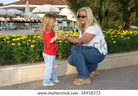 Happy mother gives her daughter a flower in a Turkish hotel - stock photo